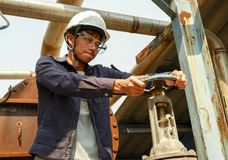 Asian guy Wearing a helmet Rotating the water pipe valve In the production process stock photo