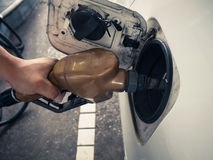 A asian hand is filling the gasoline to a car Stock Photos