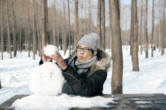 Asian handsome guy building snowman in garden Royalty Free Stock Photos