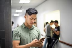 Asian handsome men concentrating on smartphone | typing message on cellphone royalty free stock photos