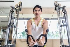 Asian handsome man exercising cable crossover for chest muscles. Low-angle view portrait of an Asian handsome man looking down with concentration while Stock Photography