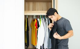An asian handsome man select shirt in cupboard stock images