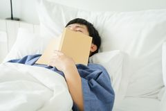Asian handsome man Read books while sleeping. Man book cover Drowsiness causes sleep.The concept of adequate sleep. Good sleep. Asian handsome man Read books royalty free stock photo