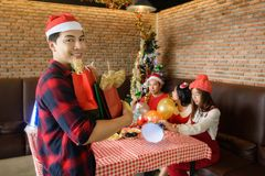 Handsome man hold christmas gifts to friends. Asian handsome men in santa hat hold many christmas presents for his friends. happy santa guy deliver xmas gifts royalty free stock images