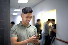 Asian handsome men talking happily on the phone | Guy smile while typing message smartphone royalty free stock photo