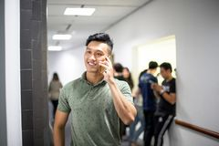 Asian handsome men talking happily on the phone | Guy smile while using smartphone royalty free stock image