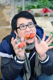 Asian handsome tourist man wearing overcoat in strawberry greenhouse Stock Images