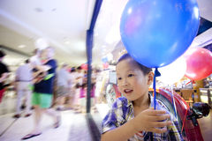 Asian happy boy in shopping mall taking a balloon Stock Photo