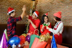 Asian happy friends in Christmas party. Group of Asian happy friends in living room with nice Christmas decoration celebrate Xmas party. New year holiday party royalty free stock photos