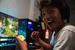 Asian happy gamer boy rejoicing while playing video games on sma. Rtphone and computer in dark room wearing headphones and using backlit colorful keyboard royalty free stock photo