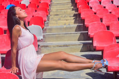 Asian Happy model posing at the stadium sitting on brigh Royalty Free Stock Photography