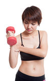 Asian healthy girl got arm pain with dumbbell. Stock Image