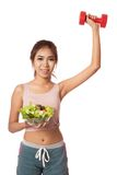 Asian healthy girl with salad bowl and dumbbell Royalty Free Stock Image