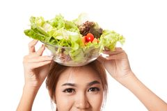 Asian healthy girl with salad bowl over head. Isolated on white background Stock Photos