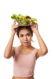 Asian healthy girl with salad bowl over head Royalty Free Stock Photo