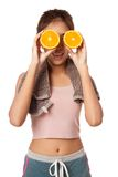 Asian healthy workout girl put orange over her eyes Royalty Free Stock Image