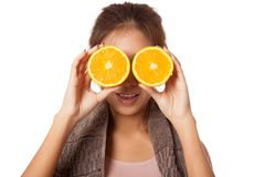 Asian healthy workout girl put orange over her eyes Royalty Free Stock Images
