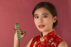 Asian hi-tech girl. Portrait of young beautiful Chinese female in traditional clothes (cheongsam) holding computer memory chip by chopsticks Royalty Free Stock Images