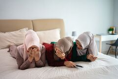 Asian hijab woman with friends cover face because of fear when watching horor film