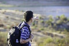 Asian hiker pointing at a lake Royalty Free Stock Image