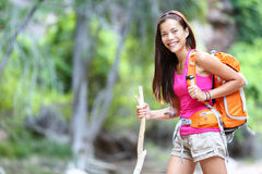 Asian hiking woman portrait. Female hiker in forest standing with walking stick looking at camera Royalty Free Stock Photography