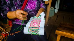 Asian hill tribe woman embroidering traditional handicraft. Fabric for decorate local homemade clothes stock images