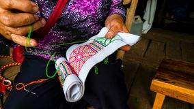 Asian hill tribe woman embroidering traditional handicraft stock photo
