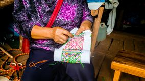 Asian hill tribe woman embroidering traditional handicraft. Fabric for decorate local homemade clothes royalty free stock photography