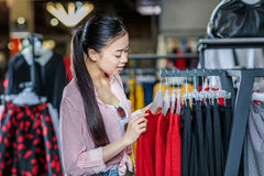 Asian hipster girl choosing clothes in shopping mall Stock Photos