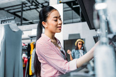 Asian hipster girl choosing clothes in shopping mall. Boutique shopping concept Royalty Free Stock Photos