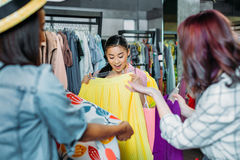 Asian hipster girl with friends choosing clothes in boutique. Fashion shopping girls concept Stock Photo