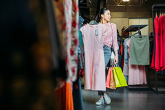 Asian hipster girl holding dress and shopping bags in boutique. Clothes shopping concept Stock Photography