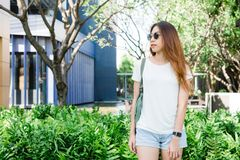 Asian hipster girl long brown hair in white blank t-shirt is standing in the middle of street. A female in street wear is standing on a green urban background royalty free stock photos