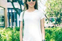 Asian hipster girl long brown hair in white blank t-shirt is standing in the middle of street. A female in street wear is standing on a green urban background stock photography