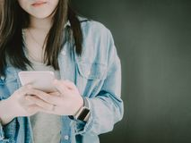 Asian hipster girl 25s to 35s with blue jacket jean during hol. D and check email and her shopping list  from her smartphone with soft focus foreground Stock Photos
