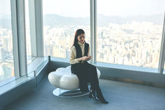 Asian hipster girl is using cell telephone, while is sitting in luxury interior against window with city view Royalty Free Stock Images