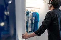 Asian hipster man choosing shirt in closet. Young Asian hipster man choosing casual style shirt oe T-shirt in closet for dressing up in bedroom. Home living stock images