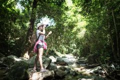 Asian hipster tourism women take a photo of waterfall in deep forest. royalty free stock image