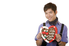 Asian holds Oktoberfest gingerbread heart Stock Images