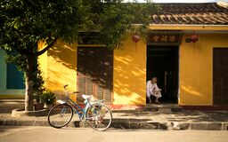 Asian Home with Man Reading Paper and Bicycle Royalty Free Stock Images