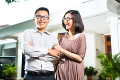 Asian Homeowner Couple In Front Of Home Royalty Free Stock Image