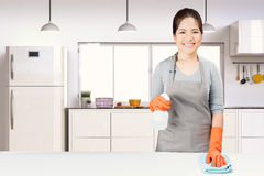 Asian housekeeper cleaning on table. With kitchen background royalty free stock images