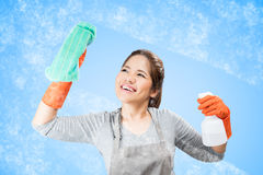Asian housewife cleaning glass Royalty Free Stock Photo