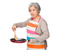 Asian housewife frying with skillet Stock Photo