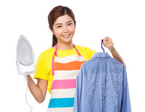 Asian housewife hold iron and shirt Stock Photo