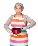 Asian housewife hold saucepan with oven glove Royalty Free Stock Photography