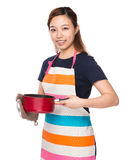 Asian Housewife holding saucepan with oven gloves Royalty Free Stock Photos