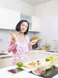 Asian housewife in kitchen Stock Photography