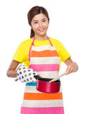 Asian housewife use of saucepan cooking. Isolated on white background Stock Image