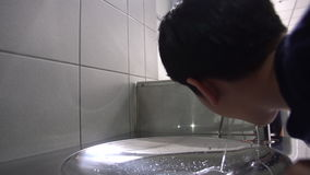 Asian hungry boy drinking water from water tube. stock footage